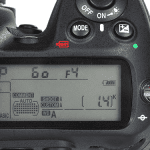 Exposure Mode and Exposure Compensation buttons on a Nikon D300 DSLR