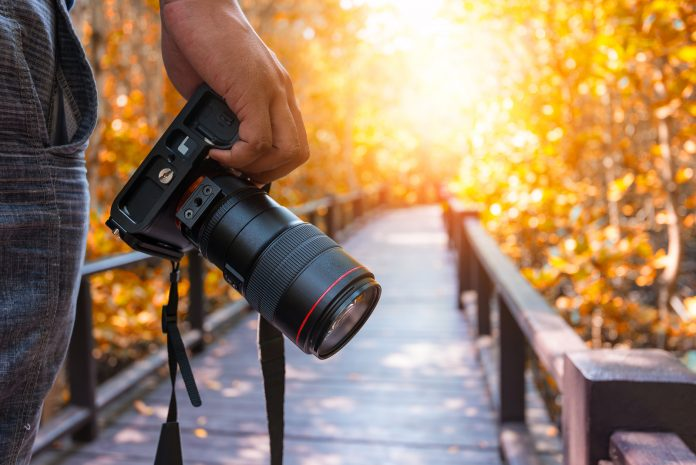 Photographer with DSLR camera on hand viewing a sunset on a bridge